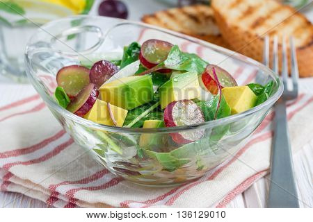 Vegetarian salad with avocado grape rucola onion with vinegar dressing in glass bowl horizontal