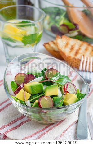 Vegetarian salad with avocado grape rucola onion with vinegar dressing in glass bowl vertical