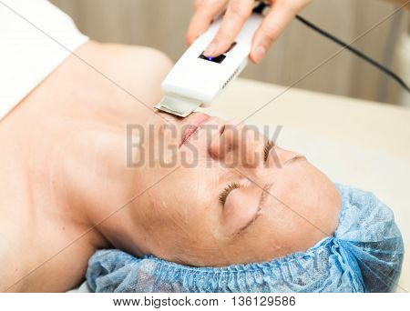 Young woman lying down in a spa salon and having a Ultrasonic face cleaning. The cosmetic procedures for the face. Beauty treatments in the spa salon. Facial Skin Care.