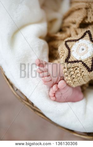 Parts of a body - pink legs of the newborn child sleeping on a white blanket in a round basket on a brown background, covered with a knitted brown blanket