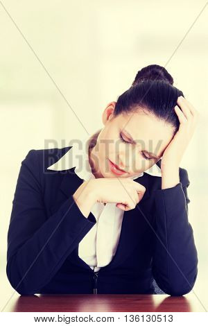 Sad business woman sitting behind the desk