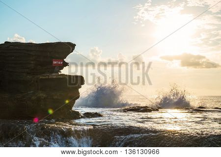 Seascape on the island with cliff and wave splashing in sunset, with sun lens flare effect