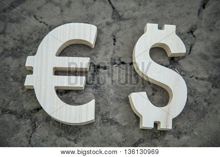 Exchange currency euro and dollar on a dry land. Wooden sign.