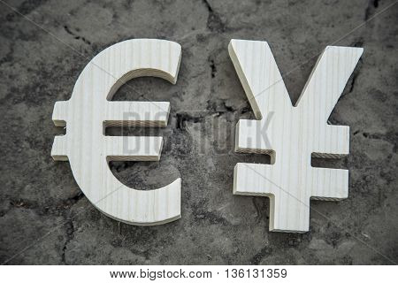 Exchange currency euro and yuan on a dry land. Wooden sign.
