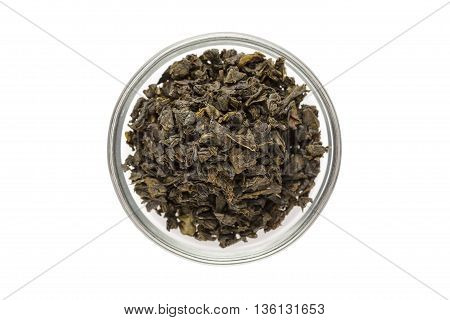 Organic Green Tea (Camellia sinensis) dried whole leaves in glass bowl isolated on white background. Macro close up. Top view.
