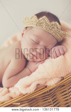 Adorable little guy with little fluffy hairs,in a beige knitted crown,tucked under his legs and put the handle under his head,sound asleep on the soft beige blanket in a large wicker basket high,sweet sleeping newborn baby
