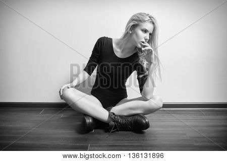 blond girl in black bodysuit and male boots sitting on floor monochrome