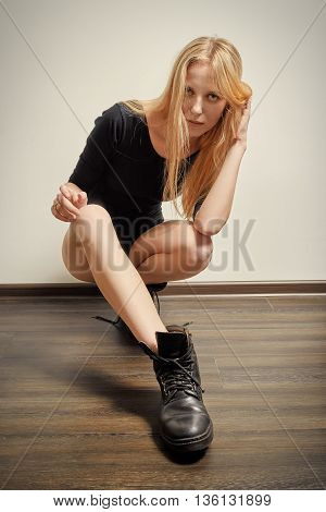 blond girl in black bodysuit and male boots sitting squat on floor