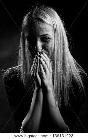 woman with smeared cosmetics crying on black background monochrome