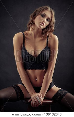 sensual woman in lingerie on black background sitting
