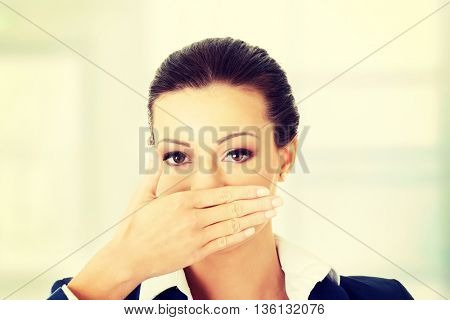 Business woman covering with hand her mouth,
