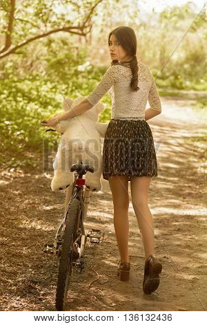 fun girl with teddy bear on bike in park