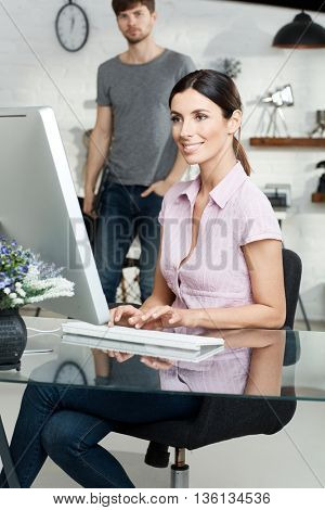 Young woman sitting at desk, working with computer, smiling.