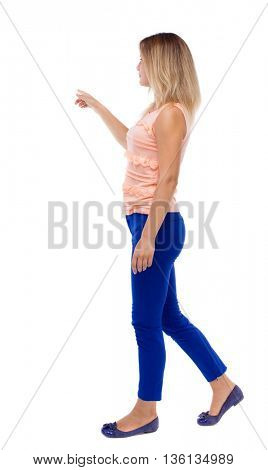 back view pointing walking  woman. going girl pointing. backside view of person.  Rear view people collection. Isolated over white background. blonde in blue pants is holding up his left hand to right