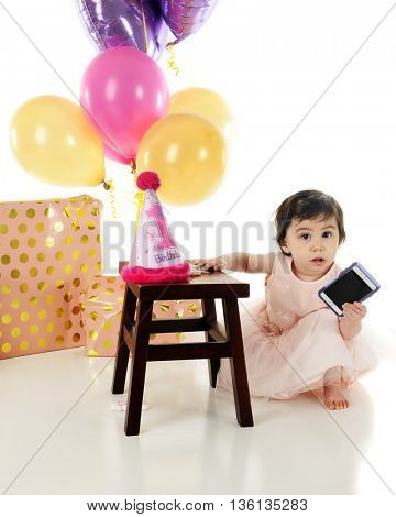 An adorable baby girl at her first  birthday celebration.  She has a smart phone in her hand and looking up at the viewer as if to ask,