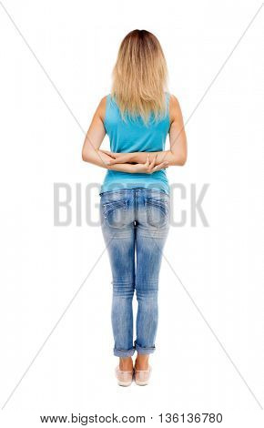 back view of standing young beautiful  woman.  Rear view people collection.  backside view of person. girl in jeans and a blue shirt stands with his arms crossed on his back.