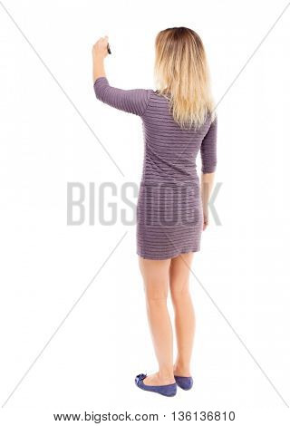 back view of writing beautiful woman. Young girl in dress. Rear view people collection.  backside view person. Isolated over white background. girl in the purple dress draws a felt-tip pen on the wall