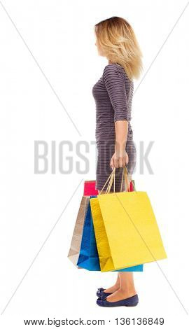back view of woman with shopping bags . beautiful brunette girl in motion.  backside view of person. Girl in purple dress is standing sideways and holding shopping bags.