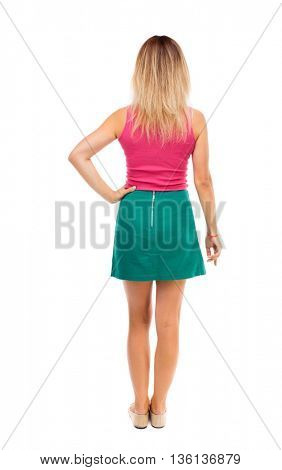 back view of standing young beautiful  woman.  girl  watching. Rear view people collection.   Isolated over white background. Blond girl in a green skirt is resting his hand on the hip.