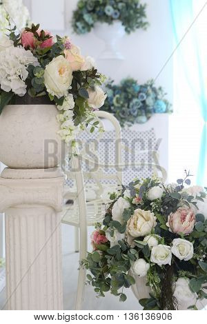 a bouquet of artificial flowers in the vase on the column
