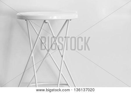 White metallic stool over a white wall. Copy space. Horizontal