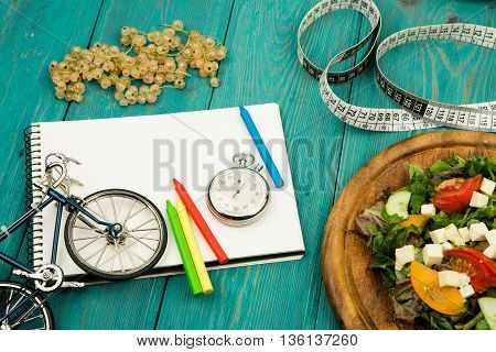 Bicycle Model, Salad Of Fresh Vegetables, Red Notepad, Stopwatch And Tape Measure On A Blue Wooden T