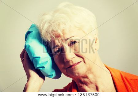 An old lady with ice bag by her head.