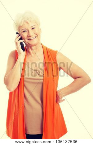 An old woman talking through phone.