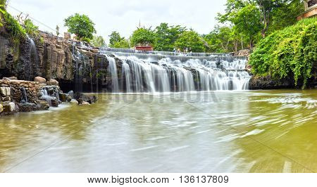 Side rock waterfall with water flowing down smooth as silk sheet stone steps make natural scenery here beautiful and lyrical, which chosen accommodation on weekend of tourists