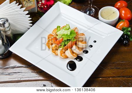 fried shrimps with salad garnish on wooden background