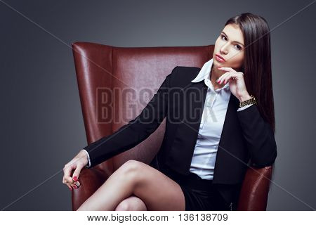 beautiful serious businesswoman with long hair in the char, isolated against grey studio background