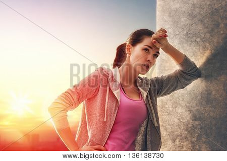 Athletic young woman running in the nature. Girl resting after an active fitness training. Healthy lifestyle.