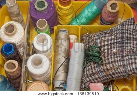 skeins of threads and needles in a box