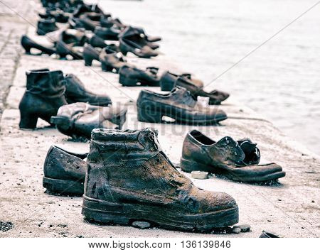 Shoes on the Danube bank is a memorial in Budapest Hungary. Blue photo filter. Shoes monument. Place of reverence. Cultural heritage. Symbolic object.