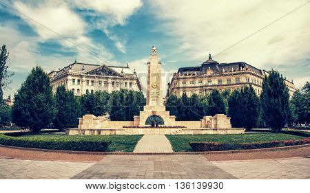 Soviet war memorial in Budapest Hungary. Cultural heritage. Architectural theme. Vintage photo filter. Travel destination. Memorial place. Wide angle photo. Memorial green trees and old buildings.