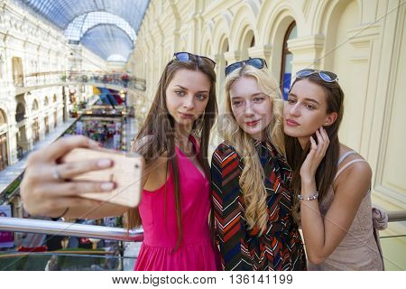 Beautiful, smiling women take a picture of herself with a smart phone. selfie, indoors shot