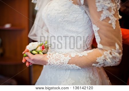 Hand of bride with boutonniere at wedding