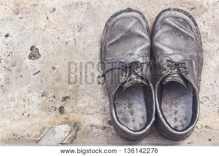 the old genuine leather shoes on concrete background