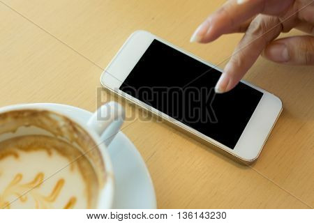 Caramel Macchiato Coffee And Woman Hand Using A Mobile Phone