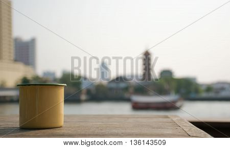 Close up Yellow cup on a wooden table next to the river.