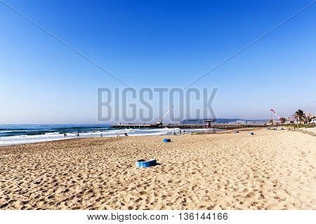 Beach With Blue Garbage Bins And Cranes On Pier