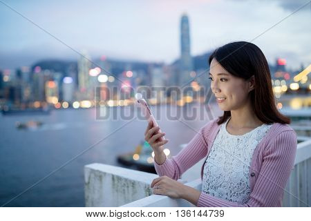 Woman hold with cellphone in Hong Kong at night