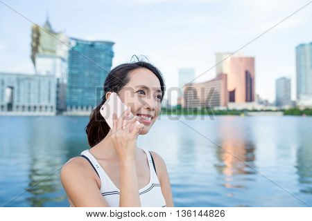 Woman talk to cellphone in Macau city