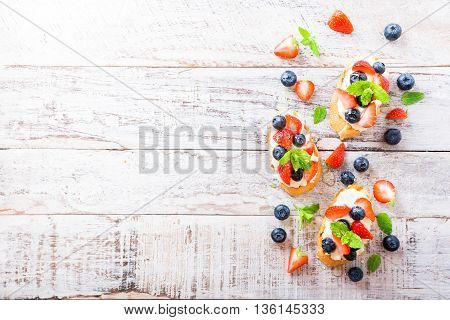 Background with crostini with grilled baguette, cream cheese, blueberry, strawberry, honey and mint on old white wooden background. Delicious appetizer or dessert. Copy space.