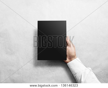 Hand holding blank black brochure booklet mockup. Leaflet mock up presentation. Pamphlet hold hand. Man show book offset paper. Sheet template. Booklet design. Paper sheet display read first person