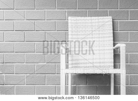 Closeup wood weave chair on blurred brown brick wall texture background beautiful interior in relaxation of house concept