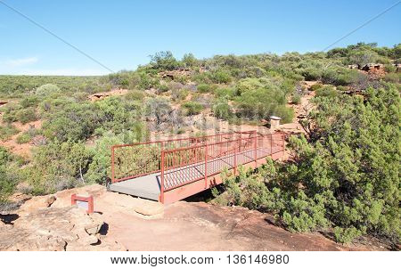 Z-bend bridge between the sandstone rock bluffs with native flora in the Z-bend landscape under a clear blue sky in Kalbarri National Park in Western Australia.