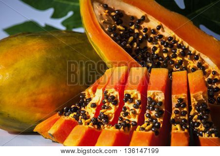 Ripe papaya and slices with seeds and green leaf
