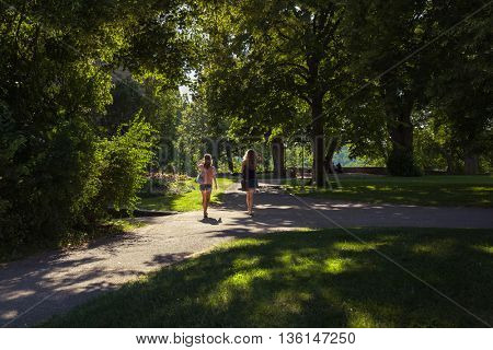 Two young women walking on path in city park