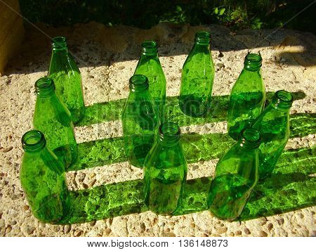 10 green bottles in the form of a number 10 sitting on a wall, depicting a UK nursery rhyme.